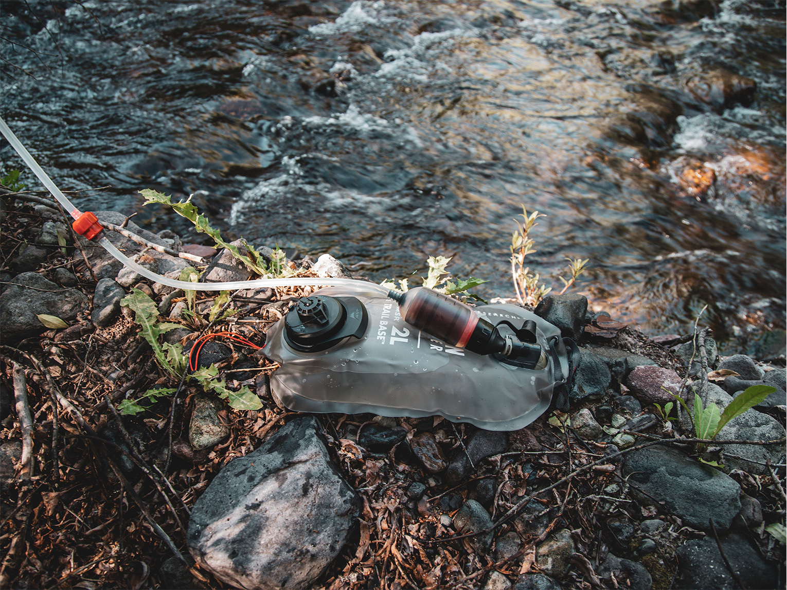 MSR 2L Trail Base Water Filter kit on ground by river