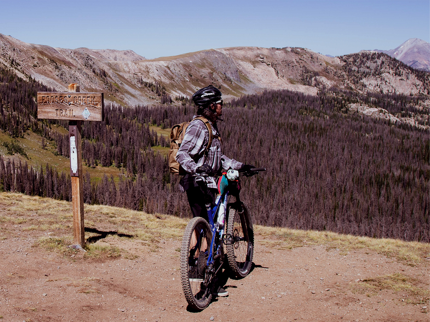 Man standing looking off into mountains with bike