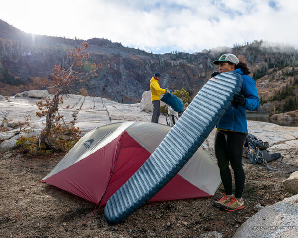 Woman blowing up thermarest sleeping pad