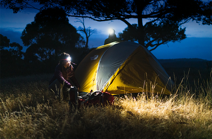 Woman at tent with Knog Bilby 400 Silicone Headlamp on