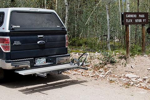 Discount Ramps Black Widow Deluxe Motorcycle Carrier on truck by sign